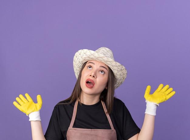 Anxieuse jolie jardinière caucasienne portant un chapeau de jardinage et des gants debout avec les mains levées levant isolées sur un mur violet avec espace pour copie