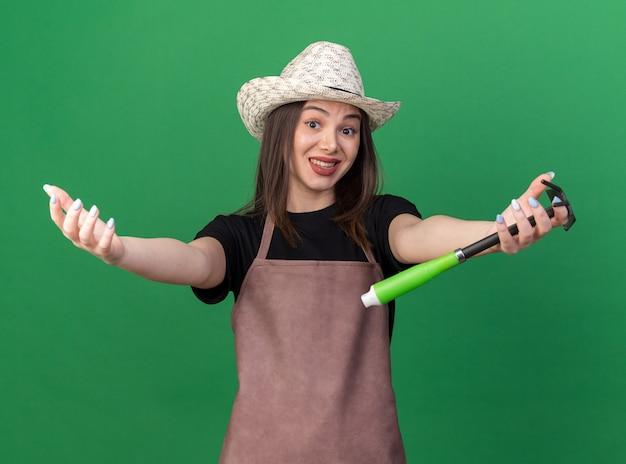 Anxieuse jolie jardinière caucasienne portant un chapeau de jardinage gardant les mains ouvertes tenant un râteau de houe