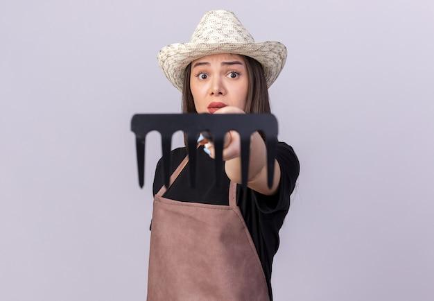 Anxieuse jolie jardinière caucasienne portant un chapeau de jardinage tenant un râteau isolé sur un mur blanc avec espace pour copie