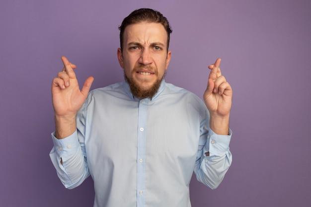 Anxieux bel homme blond croisant les doigts isolés sur le mur violet