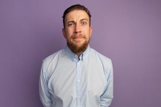 Anxieux bel homme blond regarde à l'avant isolé sur mur violet