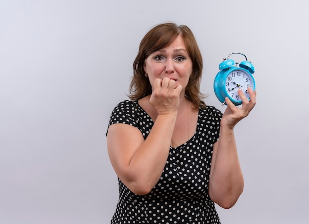 Anxieux femme d'âge moyen tenant un réveil et mordre la lèvre sur un mur blanc isolé