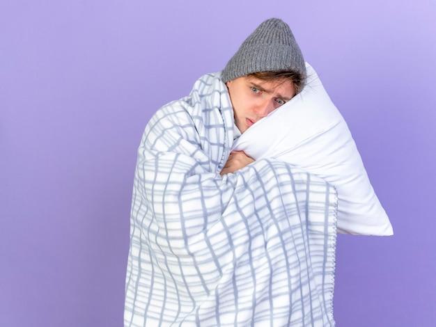 Anxieux jeune bel homme malade blonde portant un chapeau d'hiver enveloppé dans un oreiller à carreaux tenant la tête en regardant à côté isolé sur fond violet avec espace de copie