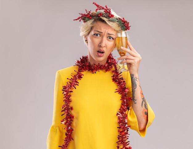 Anxieux jeune femme blonde portant une couronne de tête de noël et guirlande de guirlandes autour du cou touchant la tête avec un verre de champagne regardant la caméra isolée sur fond blanc