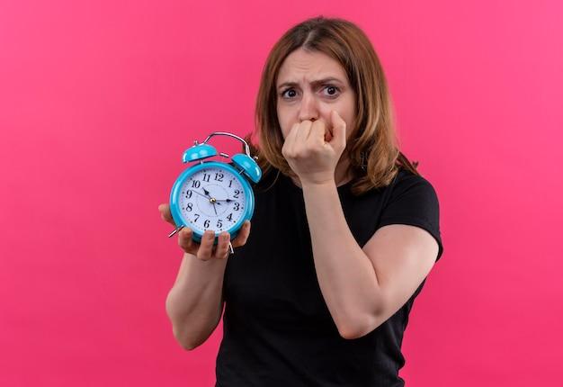 Anxieux jeune femme décontractée tenant un réveil avec la main sur la bouche sur l'espace rose isolé