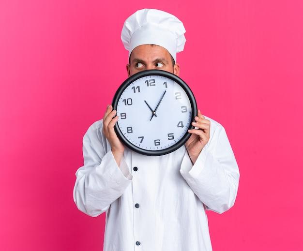 Anxieux jeune homme de race blanche cuisinier en uniforme de chef et casquette tenant une horloge regardant de côté par derrière isolé sur un mur rose