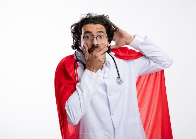 Anxieux jeune homme de super-héros caucasien à lunettes optiques portant l'uniforme du médecin avec manteau rouge et avec stéthoscope autour du cou tient la tête et met la main sur la bouche isolé sur mur blanc