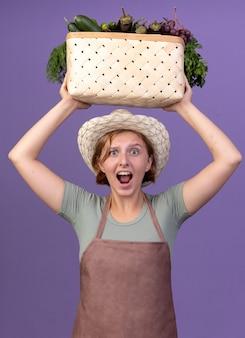 Anxieux jeune jardinière slave portant chapeau de jardinage tenant un panier de légumes au-dessus de la tête