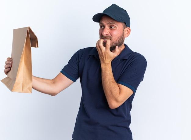 Anxieux jeune livreur caucasien en uniforme bleu et casquette étirant le paquet de papier en le regardant en gardant la main devant le menton isolé sur un mur blanc
