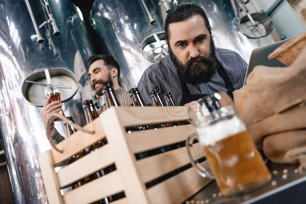Anxious brewer inspectant de la bière dans une tasse à l'usine