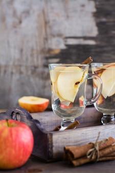 Apaisant thé à la pomme et à la cannelle dans des verres sur une table en bois. détox, antidépresseur.