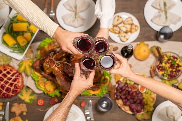 Aperçu de quatre verres de vin rouge tenus par des membres de la famille les trinquant sur une table de fête servis avec de la dinde maison et d'autres aliments
