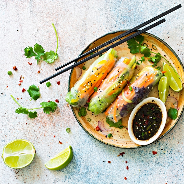 Apéritif asiatique frais rouleaux de printemps (nem) à base de papier de riz et de légumes crus et herbes avec sauce piquante sur fond bleu clair.
