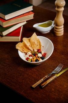 Apéritif aux champignons marinés, olives, parmesan sur une surface en bois