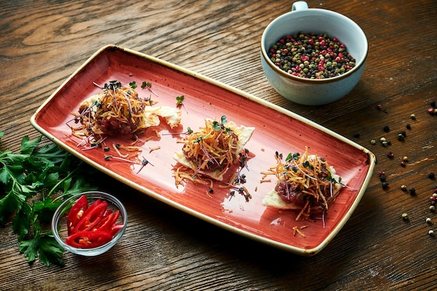 Un apéritif avant le plat principal - steak tartare de boeuf servi sur croûtons dans une assiette rouge sur une table en bois. nourriture de restaurant.
