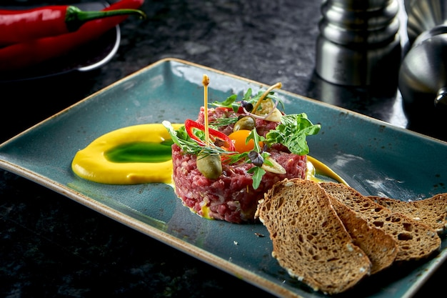 Un apéritif avant le plat principal - tartare de steak de bœuf servi avec croûtons, capsuleuses, jaunes, cornichons dans une assiette bleue sur une table en marbre. nourriture de restaurant. viande crue