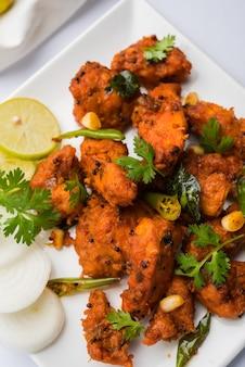 Apéritif de bar frit épicé 65 poulet ou collation rapide de l'inde dans un bol ou une assiette sur fond blanc