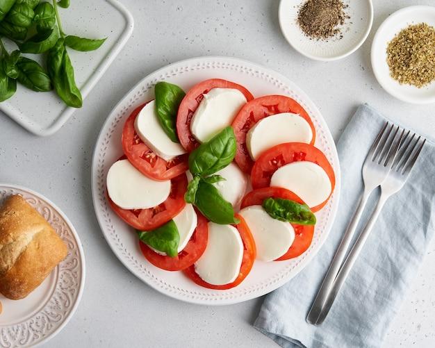 Apéritif caprese italien classique avec tomates mozzarella pain basilic et origan
