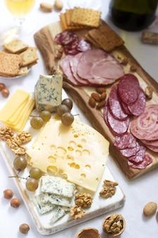 Apéritif de différents types de saucisses, viandes, fromages et craquelins sur une planche de bois, servi au vin.