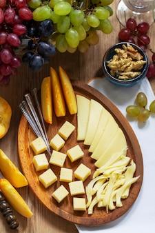 Un apéritif de divers types de fromages, raisins et noix, servi avec du vin. style rustique.