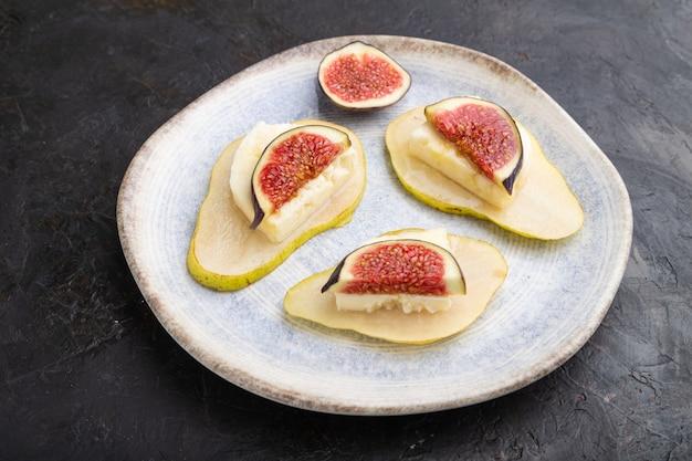 Apéritif d'été avec poire, fromage cottage, figues et miel sur plaque en céramique sur fond de béton noir. vue de côté, gros plan.