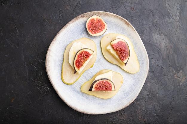 Apéritif d'été avec poire, fromage cottage, figues et miel sur plaque en céramique sur fond de béton noir. vue de dessus, mise à plat, gros plan.