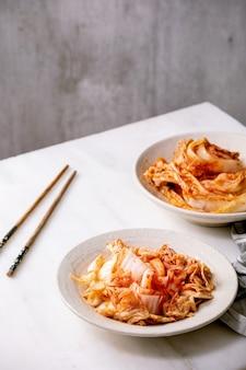 Apéritif fermenté traditionnel coréen fait maison chou kimchi entier et haché servi dans une assiette en céramique avec des baguettes sur une table en marbre blanc.