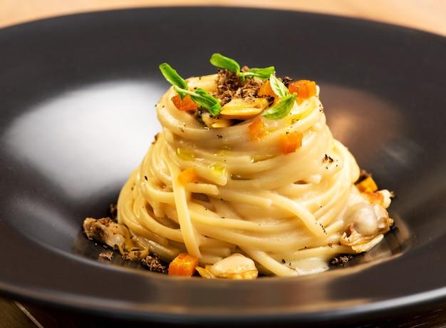 Apéritif gastronomique avec linguine, palourdes et truffes