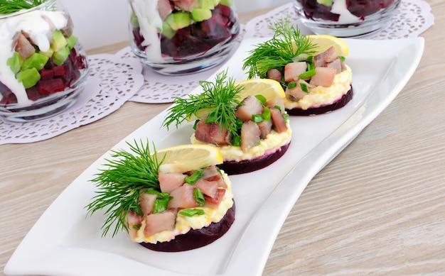 Apéritif de hareng aux oignons sur les betteraves et oeufs, citron et aneth