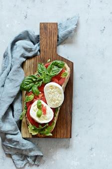 Apéritif italien bruschetta toast avec salade caprese sur une planche de bois sur fond bleu