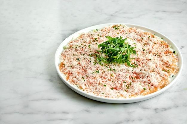 Apéritif italien classique - carpaccio de saumon à la roquette et au parmesan, servi sur une assiette blanche sur une table en marbre. saumon finement tranché. restaurant de fruits de mer.
