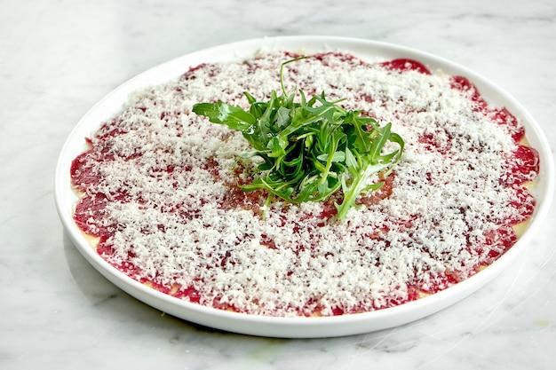 Apéritif italien classique - carpaccio de veau à la roquette et au parmesan servi sur une assiette blanche sur une table en marbre. bœuf tranché finement.