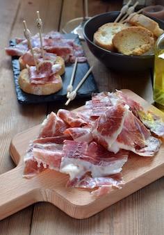 Apéritif de jambon serrano avec du pain rôti et accompagné d'un verre de vin
