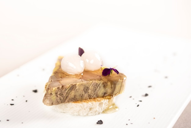 Apéritif de luxe avec foie de canard, oignons, sauce sucrée et pain grillé