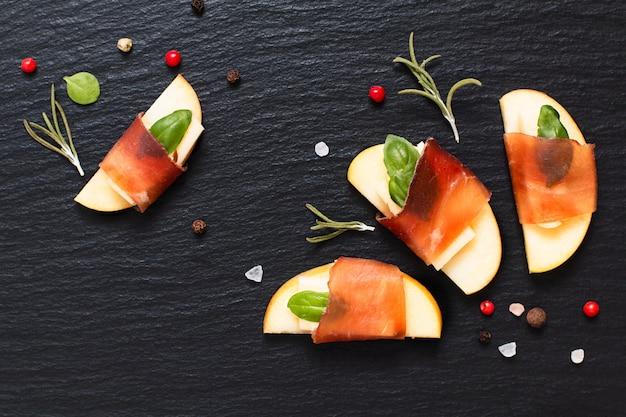 Apéritif de noël, bœuf séché aux pommes, au brie et au brie séché sur une plaque d'ardoise noire