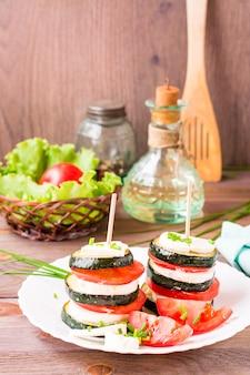 Apéritif original de courgettes frites avec tomates fraîches et fromage feta