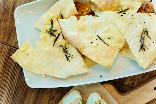 Apéritif de pain pita cuit à l'huile d'olive et au romarin sur une plaque blanche sur une table en bois.
