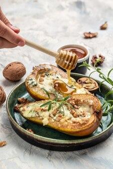 Apéritif à la poire cuite au fromage bleu, noix versant du miel. cuisine française. régime céto. délicieux petit-déjeuner ou collation, alimentation propre, régime, concept de nourriture végétalienne. vue de dessus,