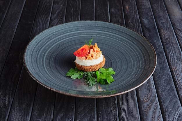 Apéritif à la réception. viande, ricotta et morceau de cerise tomate sur du pain brun