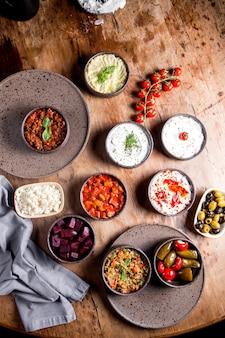 Apéritif avec salades, olives, cornichons, betteraves hachées, tomates, fromage et yaourt