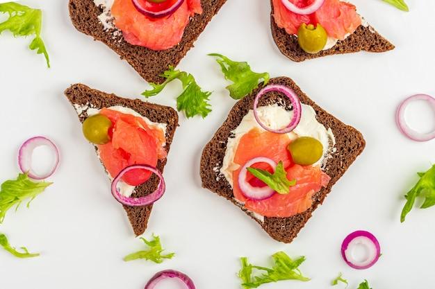 Apéritif, sandwich ouvert avec saumon et oignon sur fond blanc. cuisine traditionnelle italienne ou scandinave. concept d'une bonne nutrition et d'une alimentation saine. mise en page plate