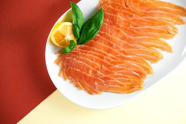Apéritif - saumon légèrement salé tranché dans une assiette blanche sur une surface lumineuse et colorée