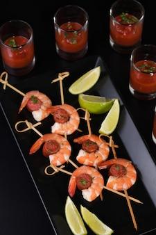 Apéritif de shish kebab aux crevettes et saucisses chorizo avec sauce barbecue dans un verre