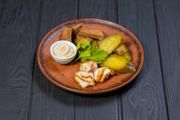 Apéritif traditionnel ukrainien de concombres marinés au bacon et pain sur une surface en bois noir