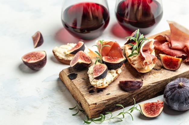 Apéritifs. antipasti, collations et vin. sandwichs au jambon, fromage cottage et figues. bruschetta traditionnelle avec jambon de parme séché et prosciutto.