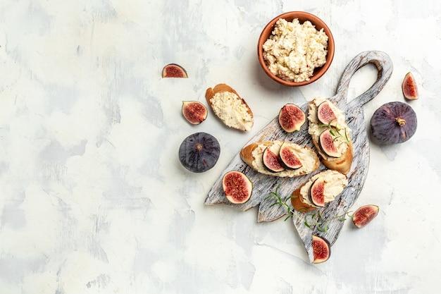 Apéritifs. bruschettas aux figues, fromage à pâte molle. délicieux petit-déjeuner ou collation, alimentation propre, régime, concept de nourriture végétalienne. vue de dessus.