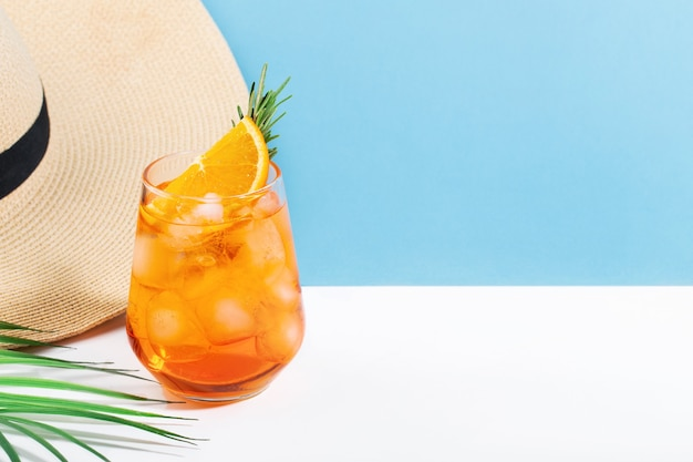 Aperol avec de la glace dans des verres et une feuille de palmier et un chapeau sur fond bleu et blanc