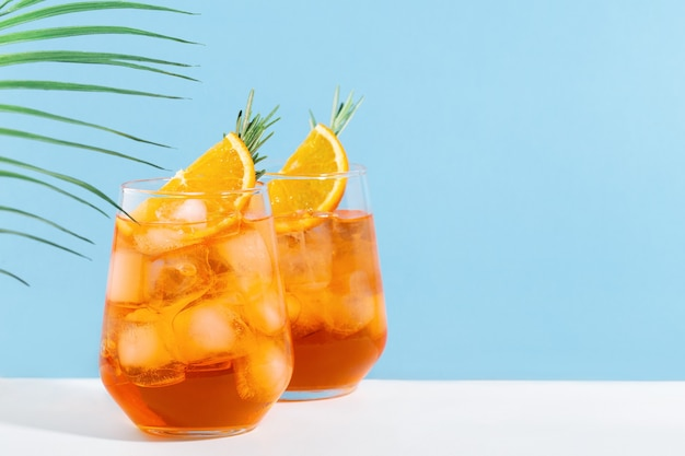 Aperol avec de la glace dans des verres et une feuille de palmier sur fond bleu et blanc