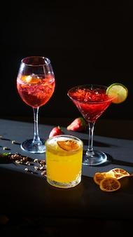 Aperol spritz et cocktails apéritifs rouges et jaunes en verre avec de la glace sur fond noir