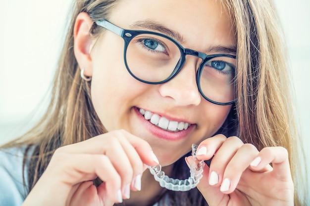 Appareil dentaire invisible ou entraîneur en silicone entre les mains d'une jeune fille souriante. concept orthodontique - invisalign.